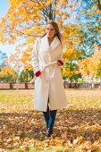 picture of overcoats  - Stylish slender young woman in an elegant white overcoat walking through an autumn park - JPG