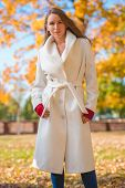 stock photo of overcoats  - Fashionable confident young woman wearing a stylish white overcoat and red mittens standing outdoors in a colorful autumn park looking at the camera - JPG