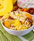 stock photo of tatar  - Fruit Pilaf with pumpkin, raisins, dried apricots in a bowl on a napkin, on a wooden boards background ** Note: Shallow depth of field - JPG