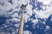 image of karts  - Big spotlight pole on blue sky background - JPG