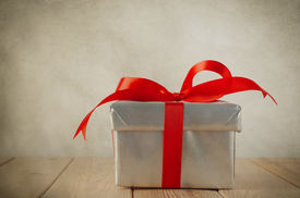 stock photo of bowing  - A Christmas gift box with closed lid wrapped in silver paper and tied to a bow with a red satin ribbon - JPG