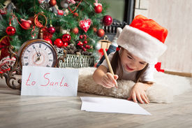picture of letters to santa claus  - Happy girl in Santa hat writes letter to Santa Claus near christmas tree and clock - JPG