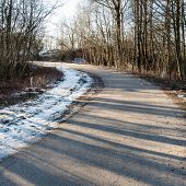 pic of icy road  - icy winter road with sun rays and trees - JPG