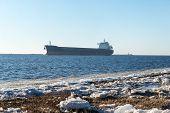 foto of shipyard  - frozen beach near shipyard and sea port with rays of sun and wavebreaker - JPG
