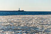 stock photo of shipyard  - frozen beach near shipyard and sea port with rays of sun and wavebreaker - JPG