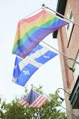 stock photo of gay flag  - A gay pride flag hanging from a building Quebec - JPG