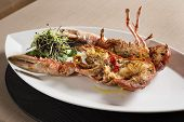 picture of lobster boat  - White plate with boat form with a lobster with vegatables - JPG