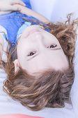 foto of upside  - Child lying upside down on white sofa - JPG