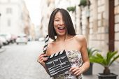 Beautiful asian woman smiling outdoor city street with clapperboard pic.