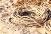 stock photo of coil  - an old coiled rope on the sand of a tropical beach - JPG