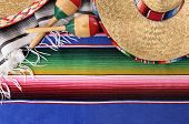 stock photo of mexican  - Mexican background with sombrero straw hat maracas and traditional serape blanket or rug - JPG