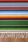 stock photo of wood craft  - Mexican background with traditional serape blanket or rug on a wood floor - JPG