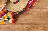 picture of sombrero  - Mexican background with sombrero straw hat maracas and traditional serape blanket or rug on a wood floor - JPG