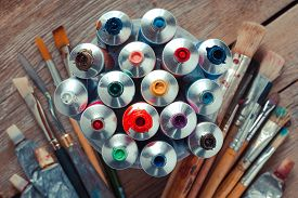 stock photo of tubes  - Vintage stylized photo of oil multicolor paint tubes closeup and artist paintbrushes on wooden desk - JPG