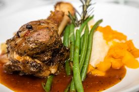pic of lamb shanks  - Roast lamb shank pn plate with green beans mashed potatoes garnished with rosemary - JPG