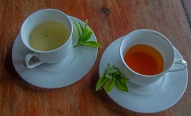 stock photo of black tea  - Green tea and fresh leavescup of tea and a natural flowerleaf tea cup black and green tea - JPG