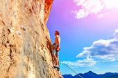 stock photo of climbing wall  - male rock climber climbs on a rocky wall - JPG