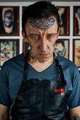 stock photo of freaky  - Freaky serious tattooed man in his studio - JPG