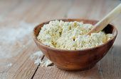 foto of chickpea  - Chickpea flour in old wooden bowl on wooden background - JPG