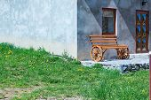 foto of windows doors  - vintage wooden bench on the wheels in front of grey house with window and door and green grass on foreground - JPG