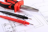 image of pliers  - Cables of multimeter and metal pliers lying on construction drawings of house electrical drawings and work tools for engineer jobs - JPG