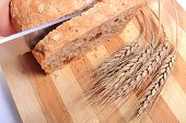 picture of fresh slice bread  - Hand of woman with knife slicing fresh baked wholemeal bread ears of wheat lying on cutting board - JPG