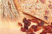 foto of fresh slice bread  - Slice of fresh baked wholemeal bread ears of wheat and heap of raisins lying on cutting board concept for healthy eating - JPG