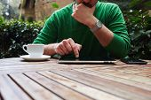 pic of coffee crop  - Cropped image male freelancer sitting at the table with cup of coffee digital tablet and smart phone man