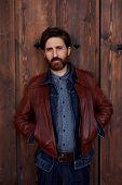 stock photo of wooden door  - Portrait of stylish hipster man with beard posing on beautiful wooden door background - JPG