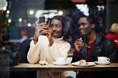 image of san valentine  - Two dark skinned friends having breakfast in cafe a woman taking the picture with digital camera on smart phone sitting in coffee shop view through cafe window - JPG
