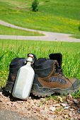 stock photo of canteen  - Hiking boots with a canteen stand on the wayside in front of a summer meadow - JPG