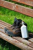 picture of canteen  - Hiking boots and a canteen on a seat bench in the nature - JPG