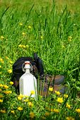 foto of canteen  - Hiking boots and a canteen are on a summer meadow - JPG