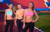 foto of race track  - athlete woman group  running on athletics race track on soccer stadium and representing competition and leadership concept in sport - JPG