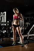 stock photo of fatigue  - fatigued beautiful girl bodybuilder rest post exercise with weight - JPG