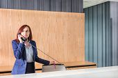 image of receptionist  - Receptionist talking on telephone in office - JPG