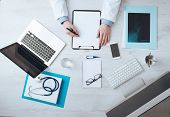 stock photo of medical equipment  - Professional doctor writing medical records on a clipboard with computer and medical equipment all around desktop top view - JPG