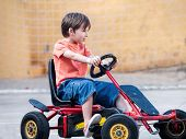 foto of pedal  - happy boy child riding a pedal cart - JPG