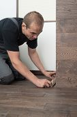 image of carpenter  - Male carpenter sets the baseboard on the floor from a massive oak Board - JPG