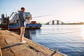 picture of street-rod  - Man casting with light rod on the river near the dock - JPG
