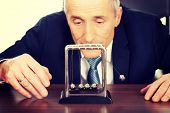 picture of newton  - Mature businessman in office playing with newton balls - JPG
