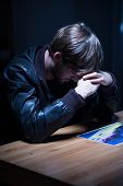 pic of interrogation  - Sad man looking at picture in interrogation room - JPG