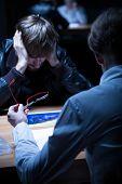 image of interrogation  - Man in black jacket questioned in interrogation room - JPG