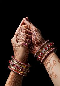 stock photo of mudra  - Woman hands with henna in shell mudra on black background - JPG