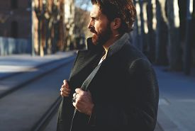 foto of mature adult  - Portrait of fashionable well dressed man with beard posing outdoors looking away confident and focused mature man in coat standing outside at sunny evening elegant fashion model - JPG