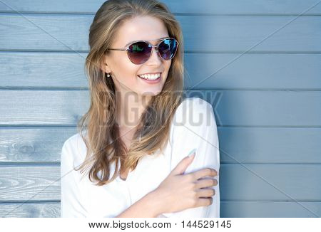 Portrait of beautiful young cheerful blonde woman with long hair wearing sunglasses and white shirt,