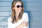 Portrait of beautiful young cheerful blonde woman with long hair wearing sunglasses and white shirt, poster