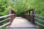 stock photo of arch foot  - An arched iron and wooden foot bridge in a park along a greenway trail as seen from end to the other - JPG