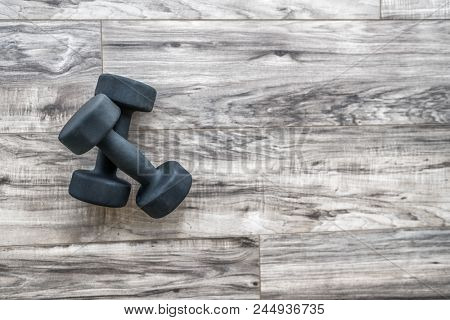 poster of Training at home fitness concept: dumbbell weights on wood floor at fitness gym . Weight loss and he