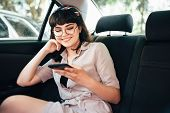 Beautiful Young Pretty Girl Is Using A Smart Phone And Smiling While Sitting On Back Seat In The Car poster